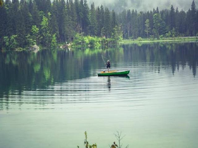 Man som fiskar från båt